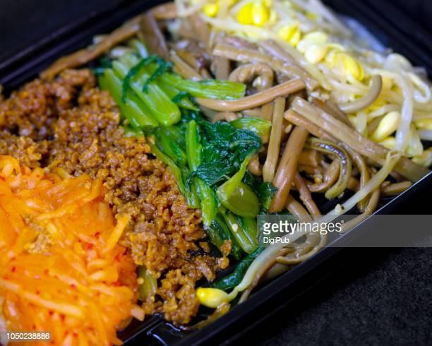 Five color Korean Namul (seasoned vegetables) in disposable plastic box on black background