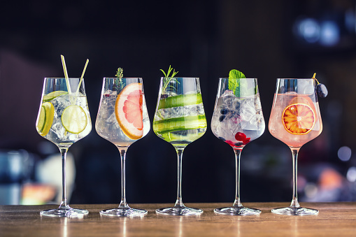 Five colorful gin tonic cocktails in wine glasses on bar counter in pup or restaurant 928321242