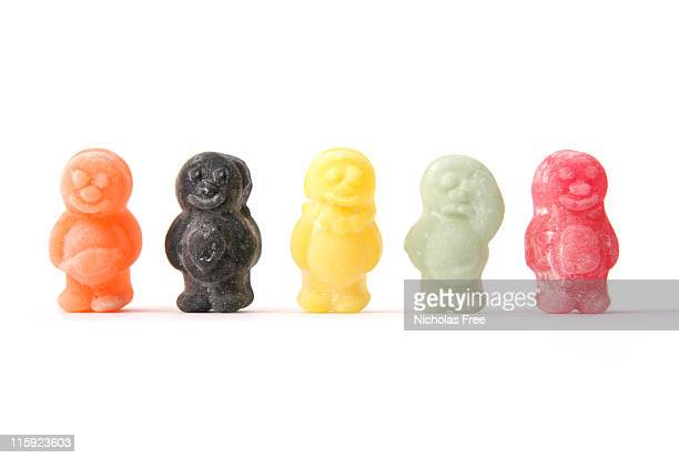 five colorful jelly babies on a white background - gelatin dessert stock photos and pictures