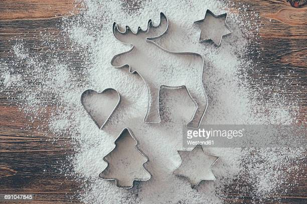 Five cookie cutters sprinkled with flour on wood