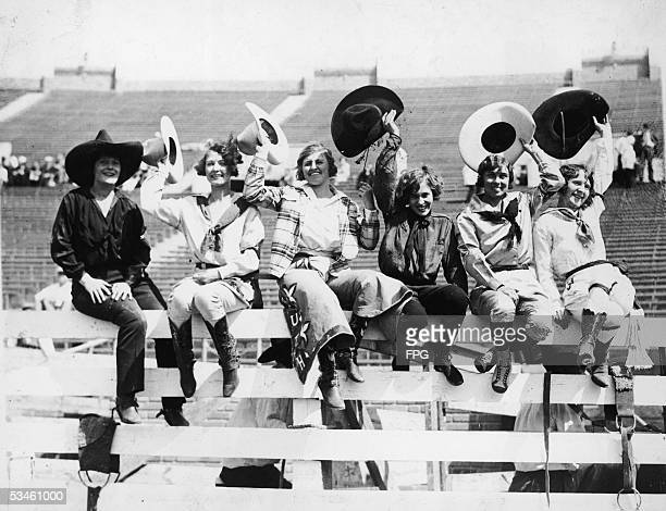 Five cowgirls sit on a fence and wave before the World's Championshi[ Rodeo at the SesquiCentennial International Exposition Philadelphia...