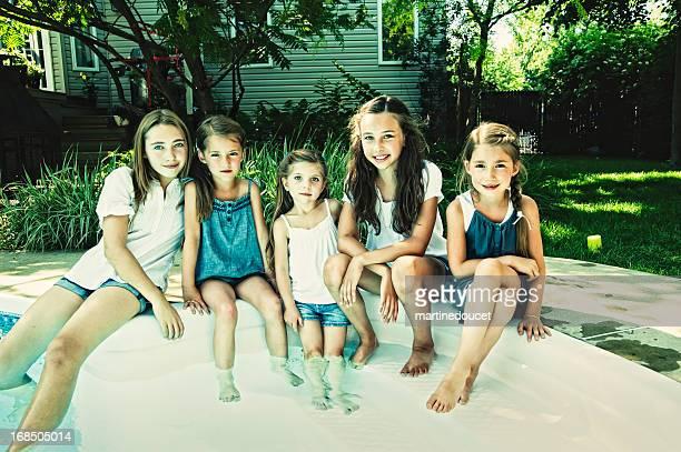 Cinco Monada niñas con pies en el patio de la piscina.