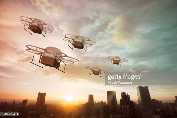 five delivery drones flying above the city at sunset - drone photos et images de collection