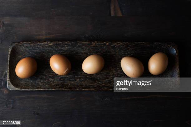 five eggs on a wooden dish - ei bruin stockfoto's en -beelden