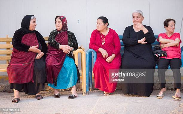Five elderly ladies sitting on bench