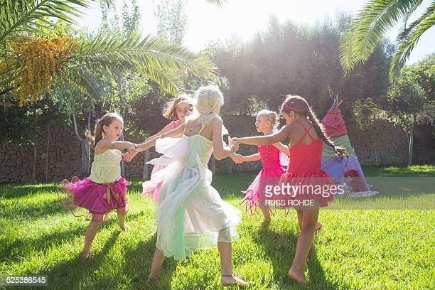 Five energetic girls in fairy costume playing in garden