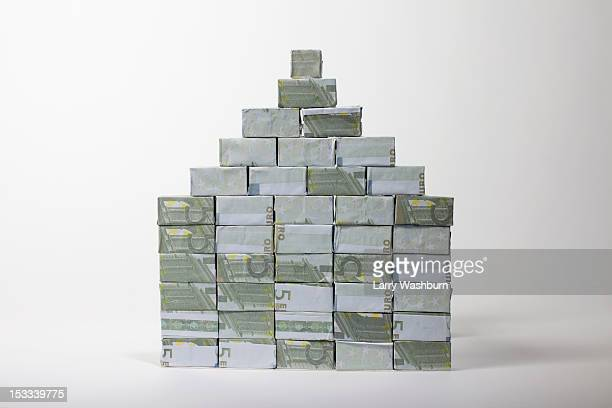 Five Euro banknotes folded into rectangular boxes and stacked into a pyramid