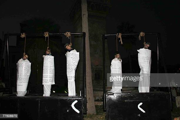 Five executed Syrian men hang from the gallows with signs detailing their crimes wrapped around their bodies in the centre of the northern town of...