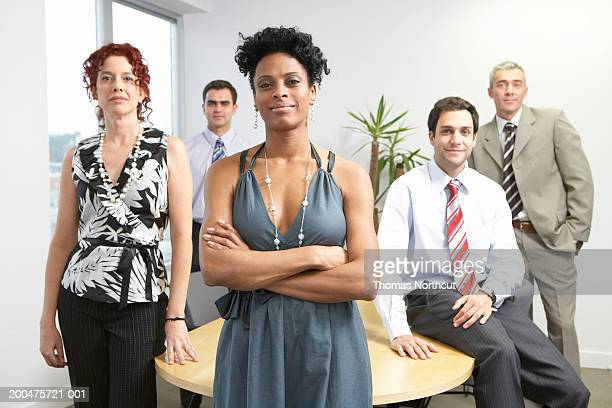 five executives in boardroom (focus on woman in foreground) - black trousers stock pictures, royalty-free photos & images