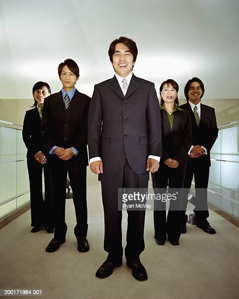 five executives standing in office corridor, smiling, portrait - 背広 ストックフォトと画像