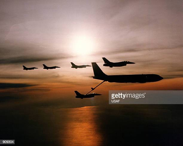 Five F16 Fighting Falcon aircraft and a KC135 Stratotanker aircraft are silhouetted against the sun during an aerial refueling operation over MacDill...