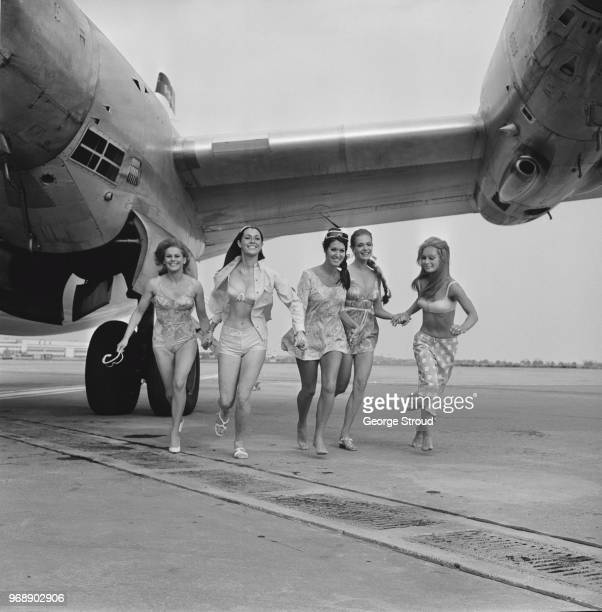 Five fashion models running near an airplane while wearing beachwear by Jantzen Heathrow Airport UK 7th July 1967 they are Marion Jenkins Sue...