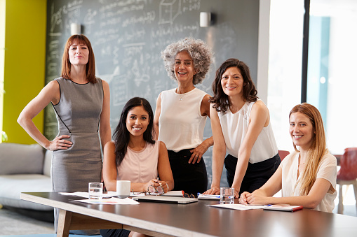 Five female colleagues at a work meeting smiling to camera 869282788