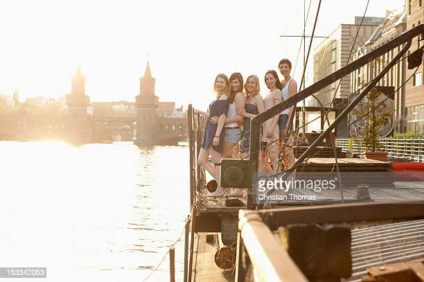 Five female friends standing in a row on a jetty, Spree River, Berlin, Germany