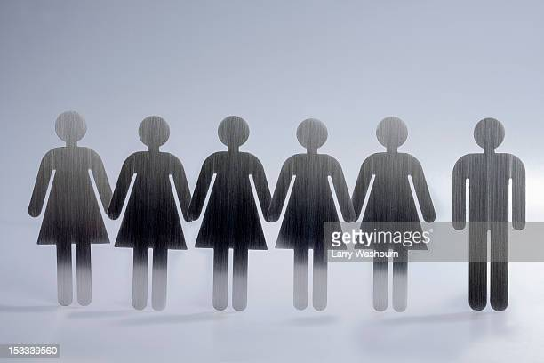 Five female restroom sign figures in a row and one male restroom sign figure