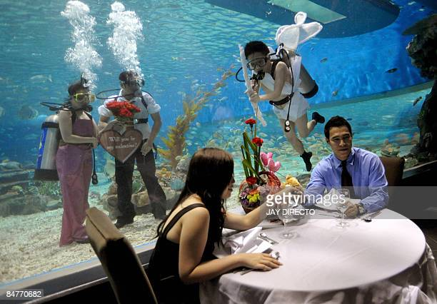 Five Filipino staff of a marine theme park on Manila Bay including three in scuba gear and attired as Cupid and two lovers strike a pose by a large...