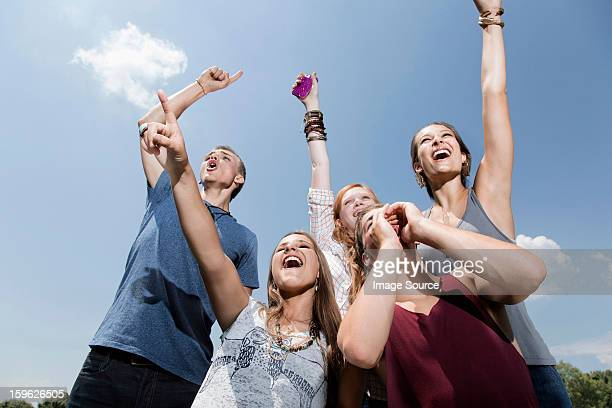 Five friends cheering, low angle