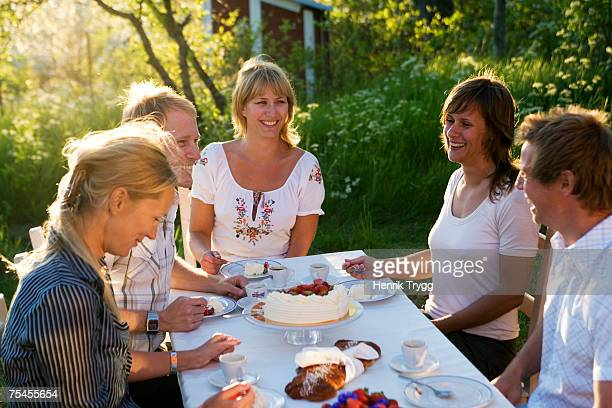 Five friends having a cake during midsummer Stockholm archipelago Sweden.