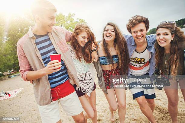 Five friends laughing with arms around each other
