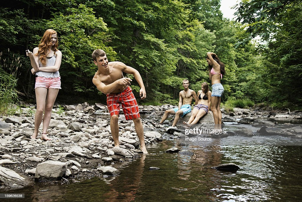 Five friends playing by river : Stock Photo