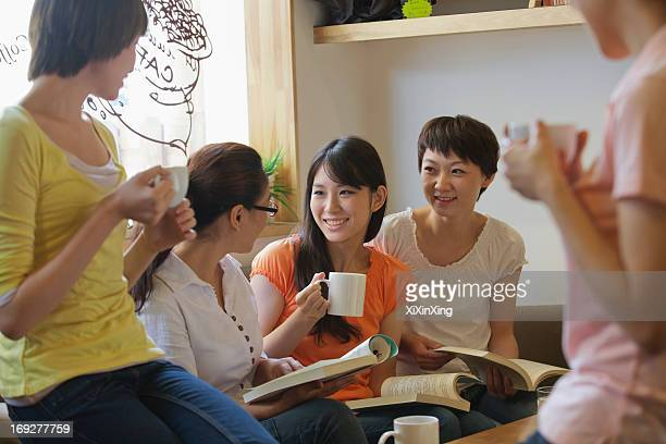 Five friends sitting in coffee shop, reading, discussing