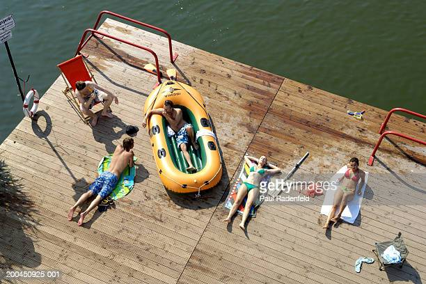 Five friends sunbathing on pier by lake, elevated view
