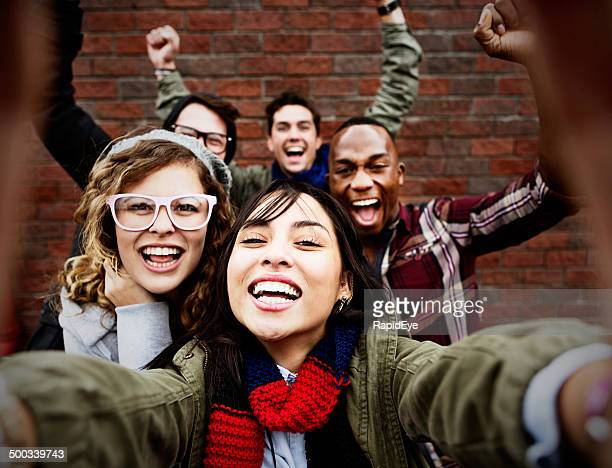 Five friends take happy, smiling selfie