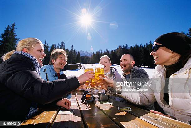 Five Friends Toasting With Lager at an Outdoors Table in the Snowy Mountains