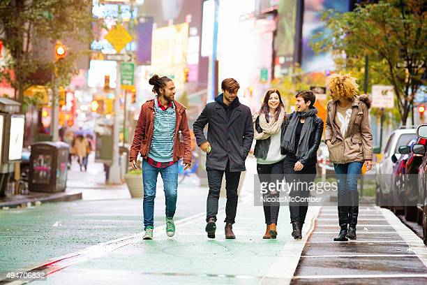 Five friends walking happy in Times square Manhattan