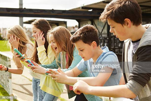 Five girls and boys in stadium stand reading smartphones