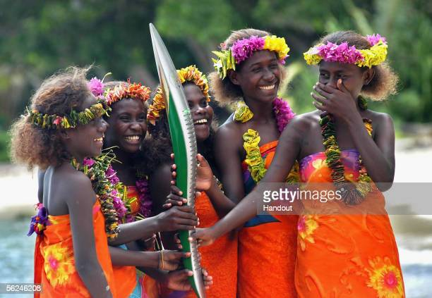 Five girls hold the Melbourne 2006 Queen's Baton on its visit to Gizo during the Solomon Islands leg of the baton's journey November 20 2005 in the...