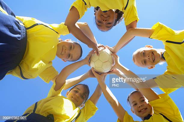 five girls (10-17) in huddle, holding soccer ball, low angle view - only girls stock pictures, royalty-free photos & images