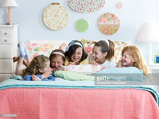five girls on a bed laughing