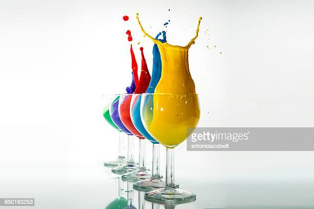 Five glasses with multi-colored acrylic paint splashing