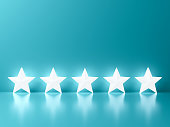 Five glowing stars standing on green blue pastel color wall background with reflections and shadows 3D rendering