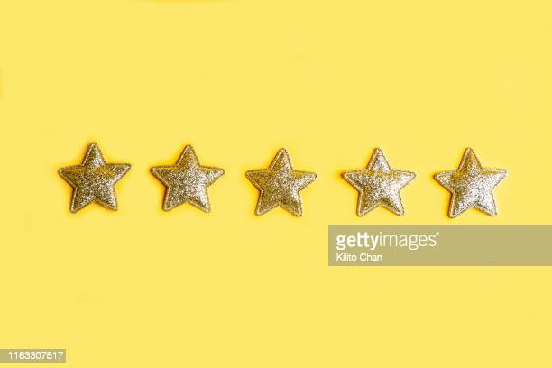 five golden stars in a line against yellow background - star shape stock pictures, royalty-free photos & images