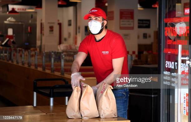 Five Guys worker brings food out to delivery drivers in Clapham as it reopens for delivery and collection on May 07 2020 in London England The UK is...