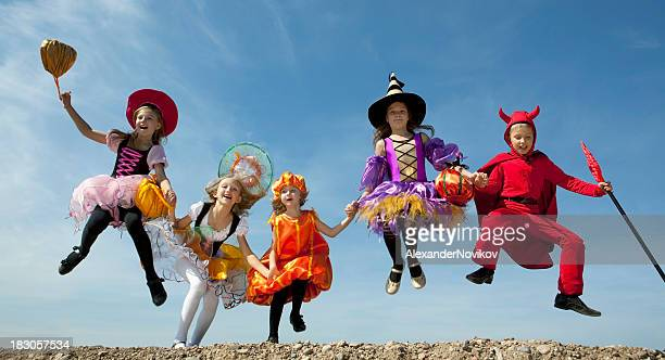 Five Halloween kids in their amusing costumes jump