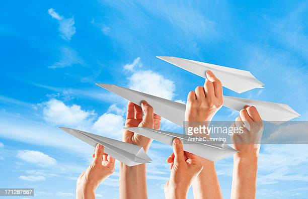 Five hands holding paper airplanes against blue sky