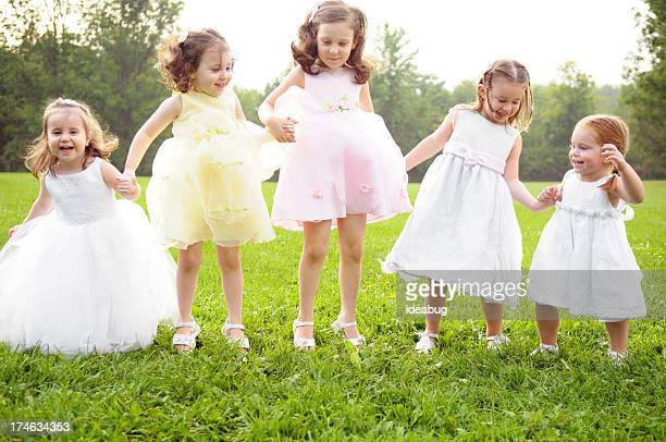 Five Happy Little Girls in Dresses Jumping Outside