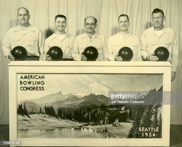 Five happy men with bowling balls and uniformed shirts pose for an American Bowling Congress group photo 1954