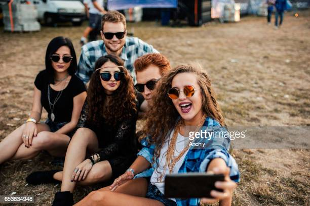Five happy teenagers sitting in the meadow taking selfie