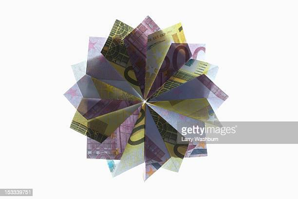 Five hundred Euro bills and two hundred Euro bills folded into a pinwheel shape