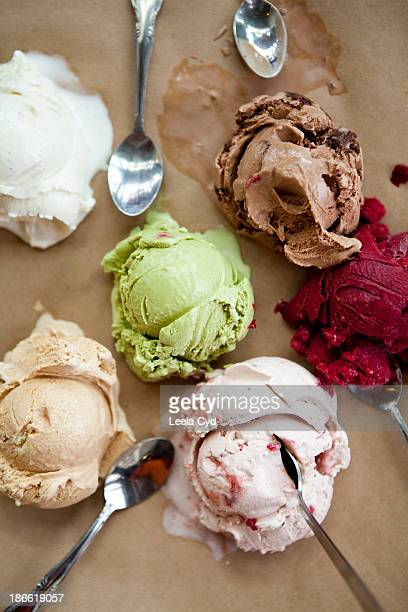 five ice cream scoops melting with spoons