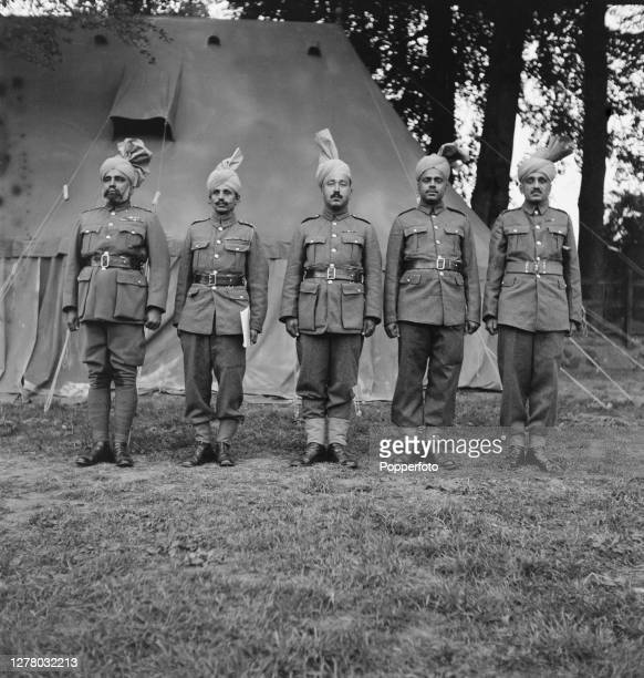 Five Indian officers from a unit of the British Indian Army stand to attention in front of a tent at their camp in the English midlands during World...