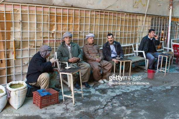 Five KurdishIraqi men some wearing traditional baggy trousers and headscarfs sit and have tea at the local bazaar of Dohuk in Iraqi Kurdistan an...
