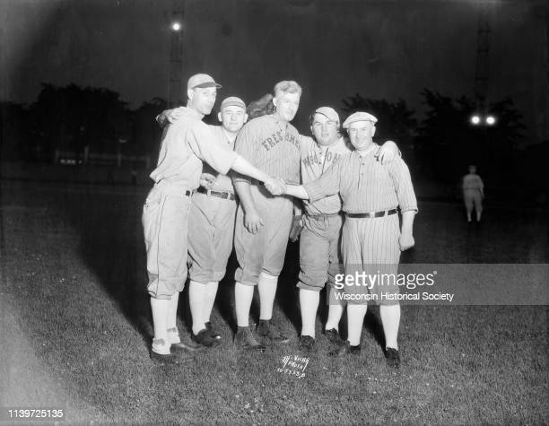 Five legislators dressed in baseball uniforms shake hands before a baseball game at Breese Stevens Field Madison Wisconsin June 25 1935 L to R...