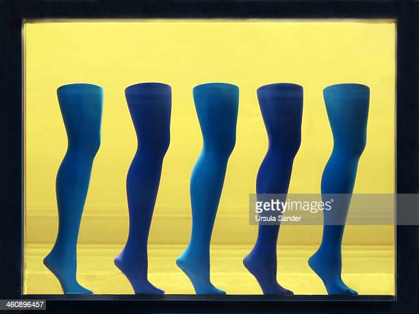 CONTENT] Five legs of mannequins on tiptoe dressed in different colored blue nylon stockings in front of a yellow background in a shop window