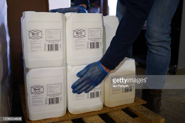 Five litre tubs of sanitising hand rub are prepared for distribution at the Whitby Gin distillery on May 20, 2020 in York, United Kingdom. Jessica...