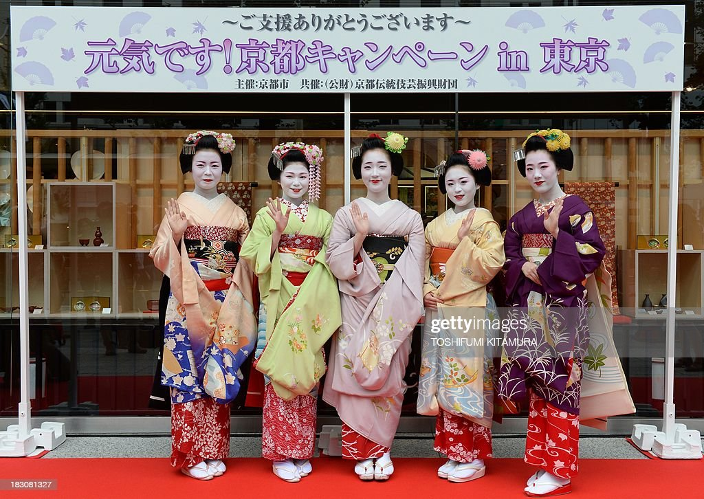 Five 'Maiko,' or apprentice geishas, (from L-R) Ichitomi from Gion Kobu, Toshitomo from Miyagawa cho, Chizu from Ponto cho, Ichimari from Kami Shichiken and Tomitae from Gion Higashi, wave in a photo session during the 'We're alive and well, Kyoto' campaign in Tokyo on October 4, 2013. As Kyoto prepares itself for the biggest sightseeing season of autumn, the girls lent their charms to lure back tourists to the 1,200-year-old city after a big typhoon flooded some of scenic spots there three weeks ago.